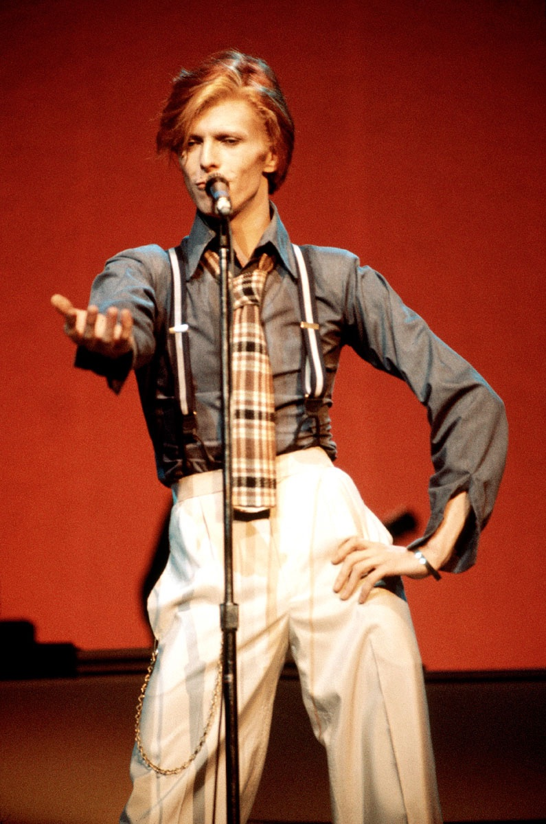 Captured in 1974, David Bowie is a chic vision in relaxed trousers and suspenders.