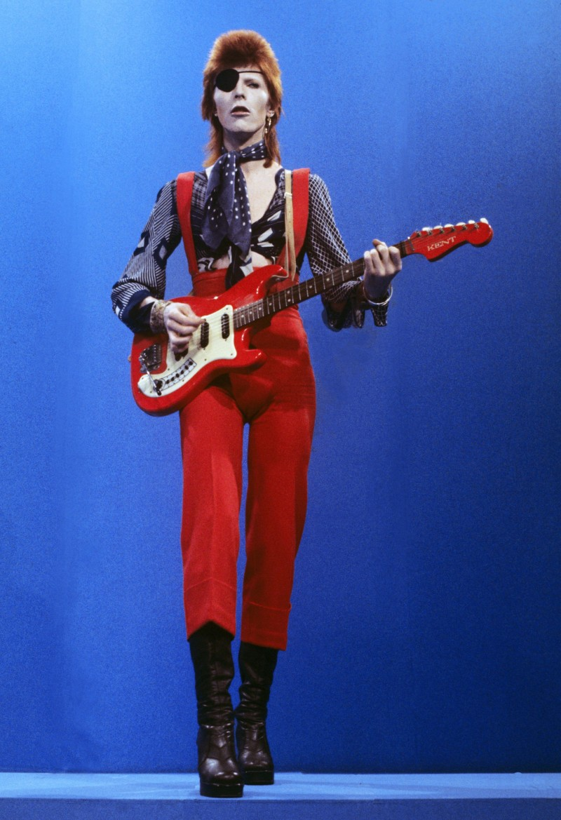 Wearing an eyepatch, David Bowie performs in a red jumpsuit and eyepatch on TopPop in 1974.