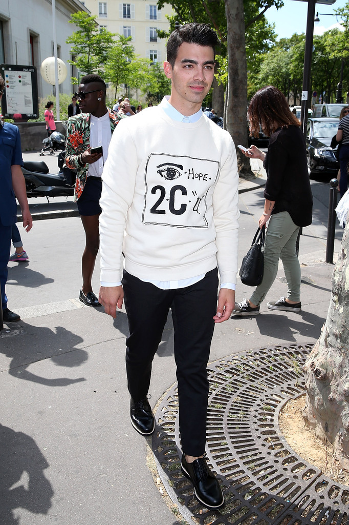 Joe Jonas checks out the first day of Paris Fashion Week. Heading to Carven's spring/summer 2015 show, Jonas wears a look from the brand featuring its 'Eye Hope 2 C U' sweatshirt.