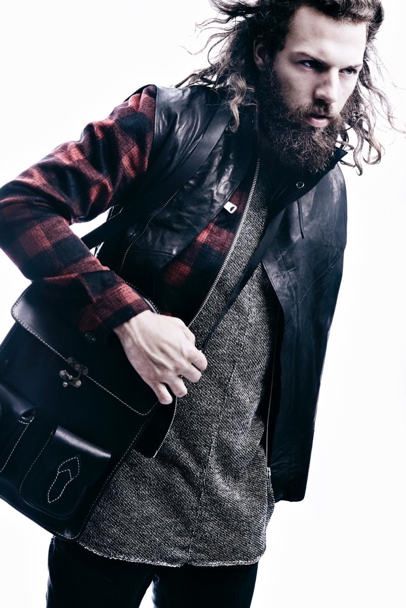 Phil wears sweater and black leather vest Daniel Patrick, flannel jacket Kill City, cross body bag Sandast and jeans Les Benjamins.