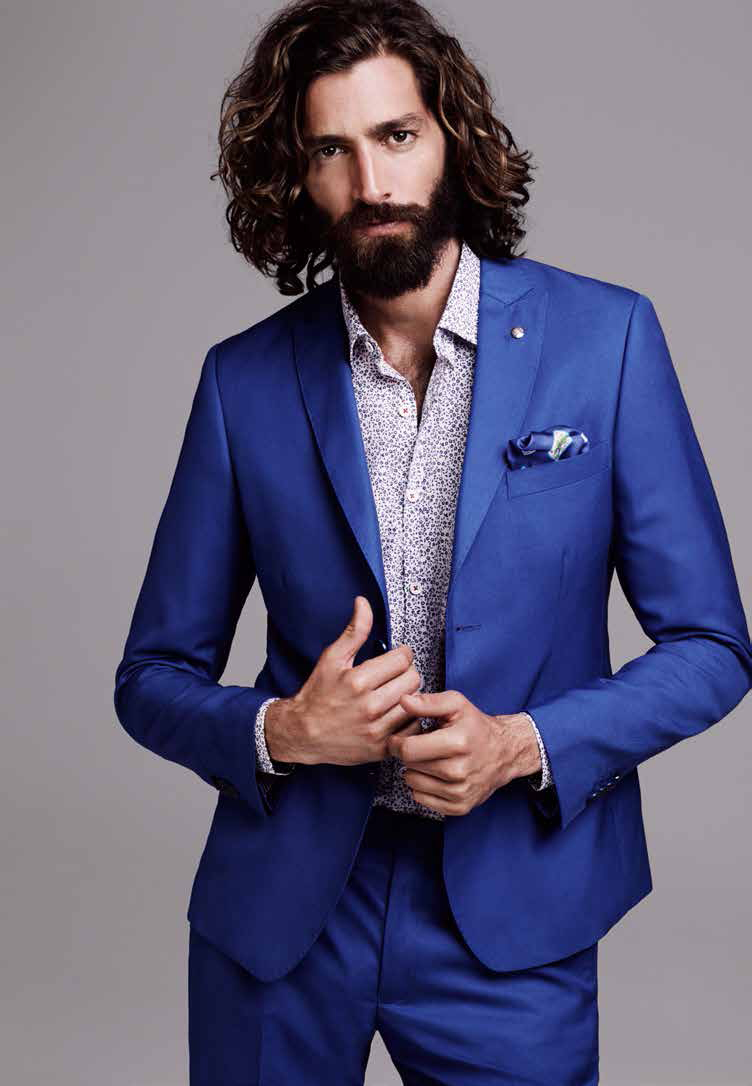 Going for a formal look to complement fine suiting, hair stylist Riad Azar assists Maximiliano Patane in achieving the perfect coif for El Palacio de Hierro. Maximiliano's wavy locks hang free as the roots are lightly brushed back for an elegant hairstyle.