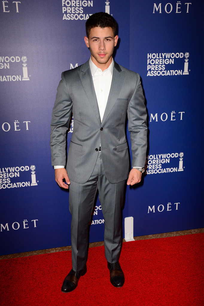 Nick Jonas cozies up to gray with a two-button suit with pleated trousers.