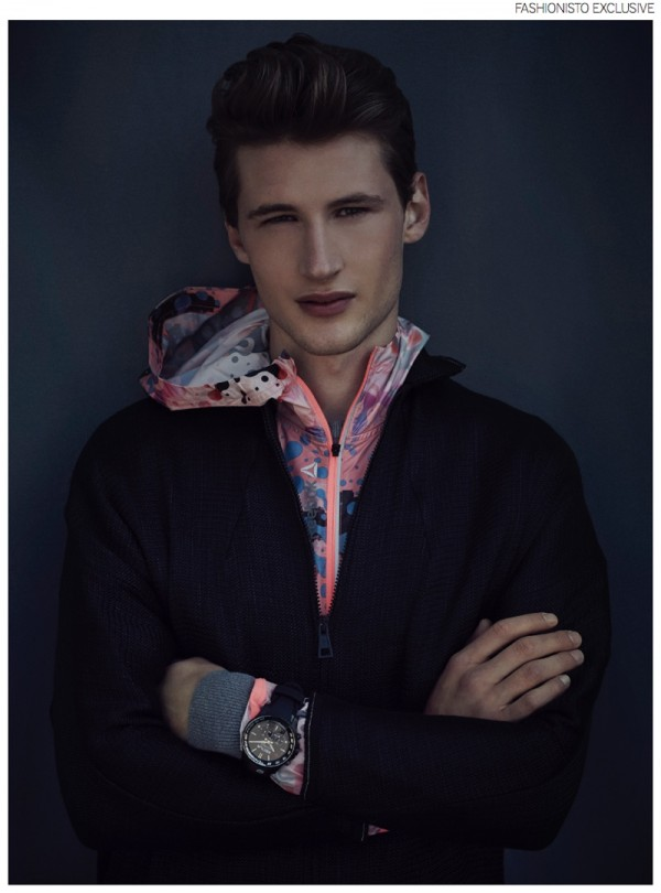 Tino wears long black coat Martin Lamothe, multi-colored windbreaker Rebok, gray jumper Fred Perry and watch Sector.