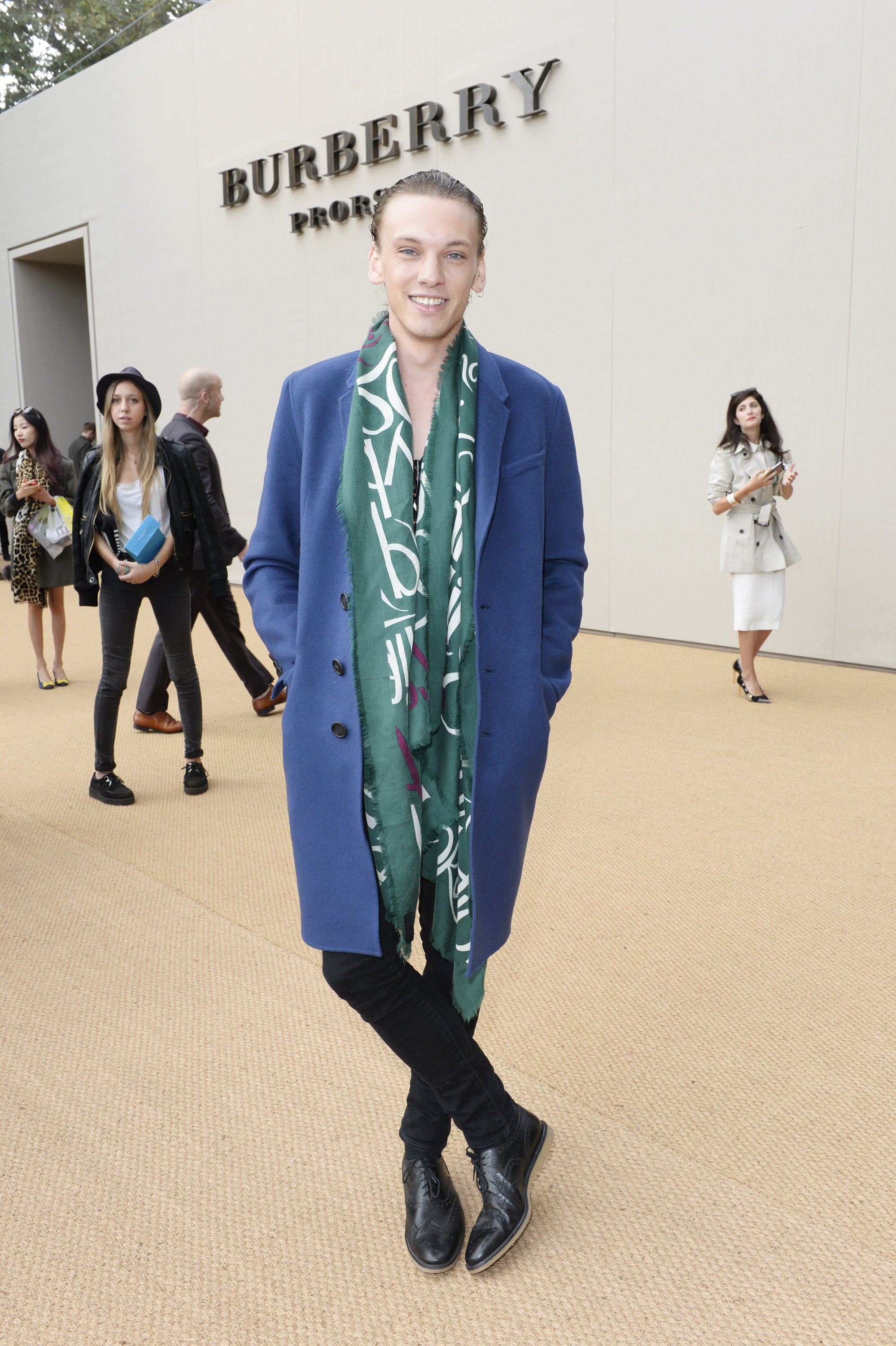 Attending Burberry's spring 2015 women's show, actor Jamie Campbell Bower wears an open Burberry Prorsum scarf with a lightweight, colorful coat.