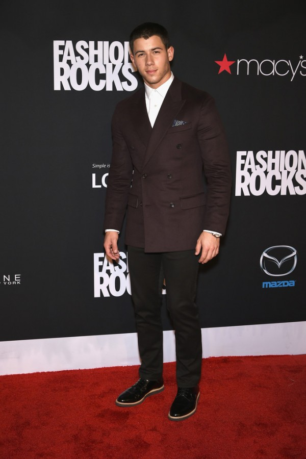Nick Jonas hits the red carpet for Fashion Rocks in a double-breasted blazer and slim-cut trousers.