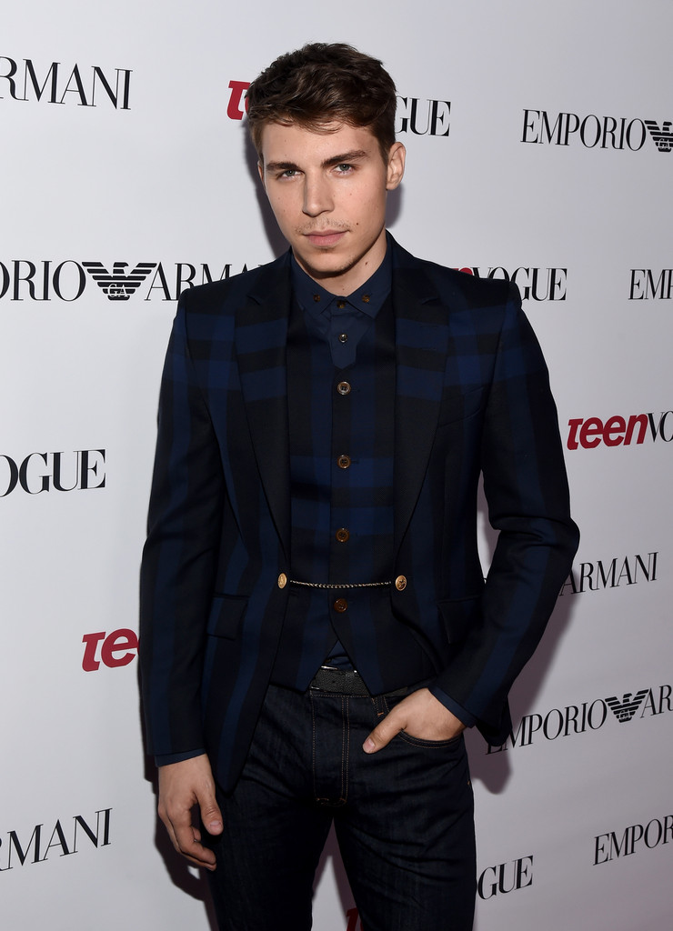 Attending Teen Vogue's 12th annual Young Hollywood party in Beverly Hills, California on September 26, 2014, actor Nolan Gerard Funk dressed to impress. For the special occasion, Funk wore a blue and black check jacket and shirt with blue denim jeans from British designer Vivienne Westwood.