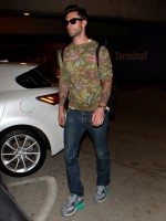 Spotted at LAX on October 24th, Maroon 5 frontman Adam Levine was casual in a pair of denim jeans, sunglasses and NIKE sneakers. Levine made a graphic statement with a floral print sweatshirt from his Kmart line.