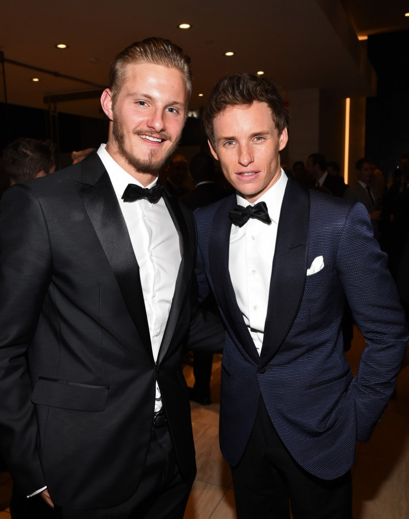 Dapper in a black tuxedo, BVLGARI brand ambassador Alexander Ludwig joins fellow actor Eddie Redmayne for a photo.