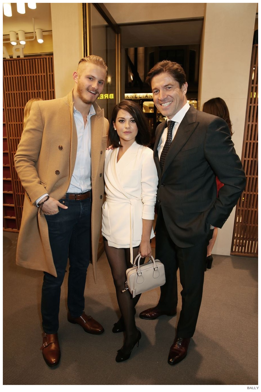 Dapper in a camel coat, actor Alexander Ludwig poses for a photo with actress Sarah Greene and Bally CEO Frédéric de Narp.