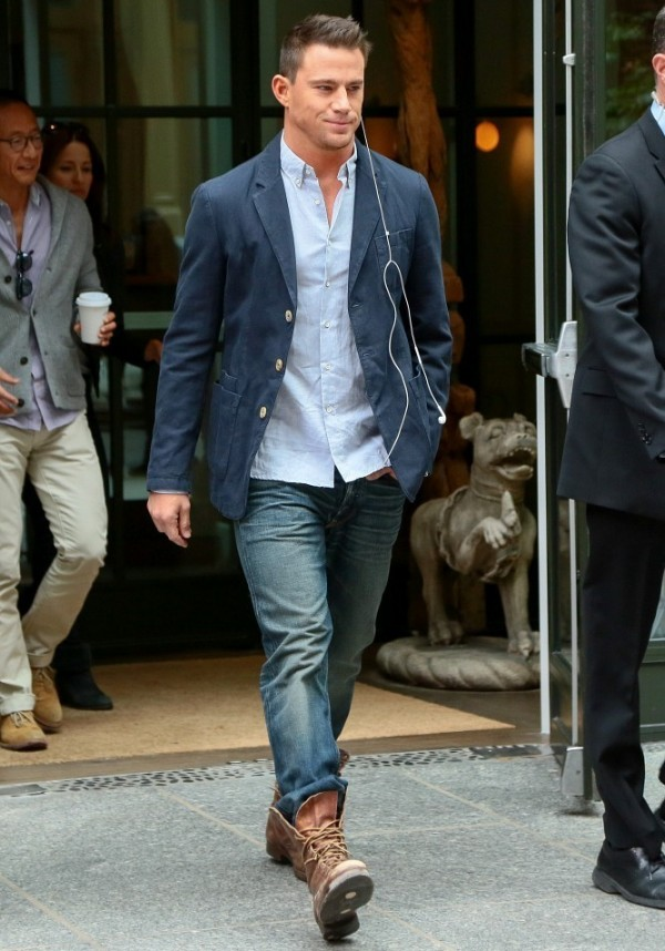 On October 10th, Channing Tatum takes a confident stroll in New York City, wearing a pair of distressed denim jeans, brown leather boots, a light blue oxford and a navy sports jacket.