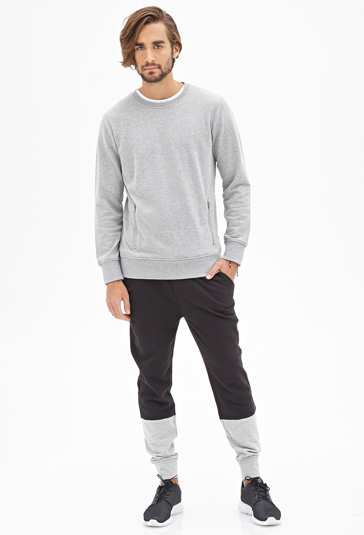 Nicolas wears black and gray color block sweatpants.