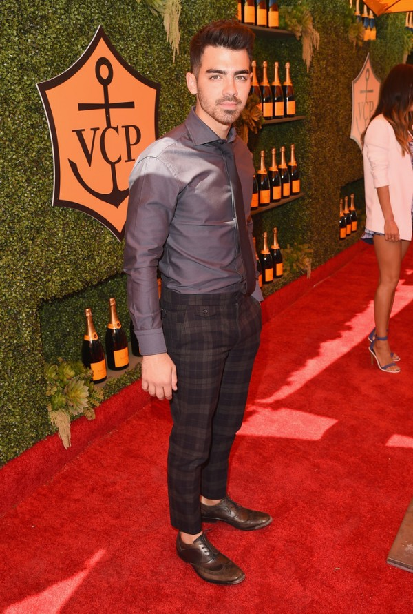 Attending the fifth annual Veuve Clicquot Polo Classic at Will Rogers State Historic Park on October 11, 2014 in Pacific Palisades, California, Joe Jonas kept his look simple with a dress shirt and tie, paired with plaid trousers and sock-less leather dress shoes.