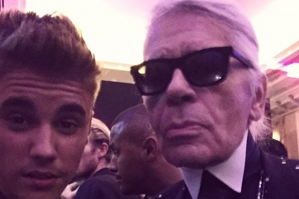 Justin Bieber poses for a photo with designer and photographer Karl Lagerfeld at a party hosted by CR Fashion Book. Pictured, Bieber wears Balmain while Lagerfeld sports Dior Homme.