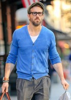 Ryan Reynolds keeps busy on October 16th, spotted in New York City outside the Greenwich hotel. Reynolds was as stylish as always in a fitted blue cardigan paired with gray trousers, a driver's cap and black frames.
