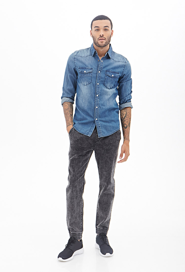 Don wears stonewash denim joggers.