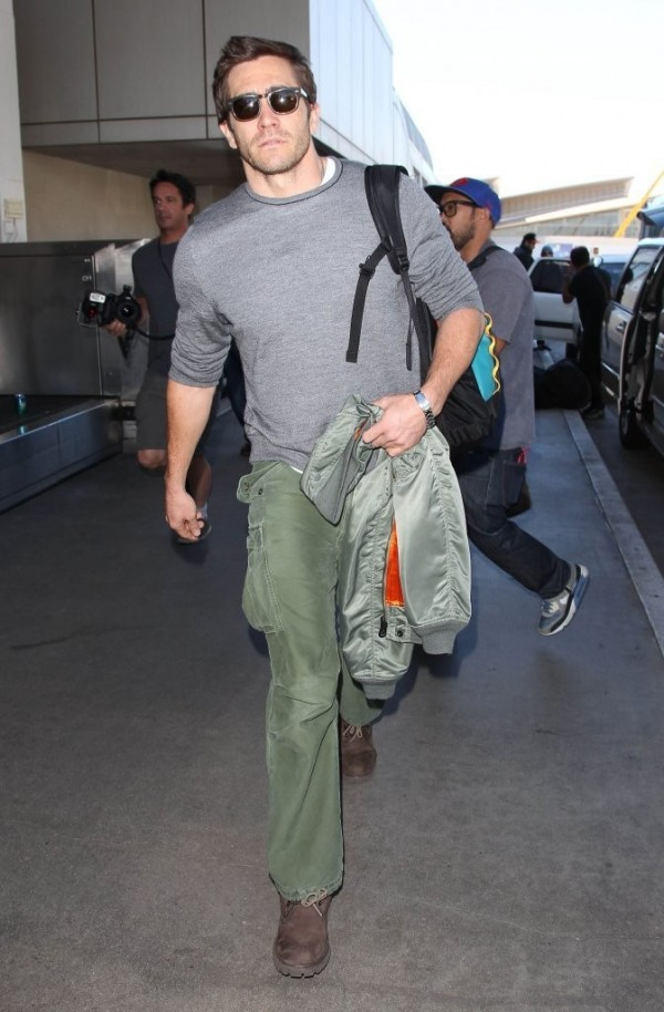 Jake Gyllenhaal departs LAX on November 4th in a pair of army green cargo pants, paired with a simple gray knit, white t-shirt, bomber jacket and brown boots.