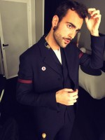 Captured backstage at X Factor Italy, Italian singer Marco Mengoni was spotted in a tailored three-piece suit from Z Zegna's fall-winter 2014 collection. The suit's colored armbands is a significant detail of this season's outing from the Italian label.