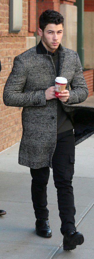 Currently promoting his self-titled album, Nick Jonas is out and about in New York City, where he was spotted on November 18th, bundling up in a coat from AMI. The tweed coat makes quite the sartorial statement with its smart black & white checks.