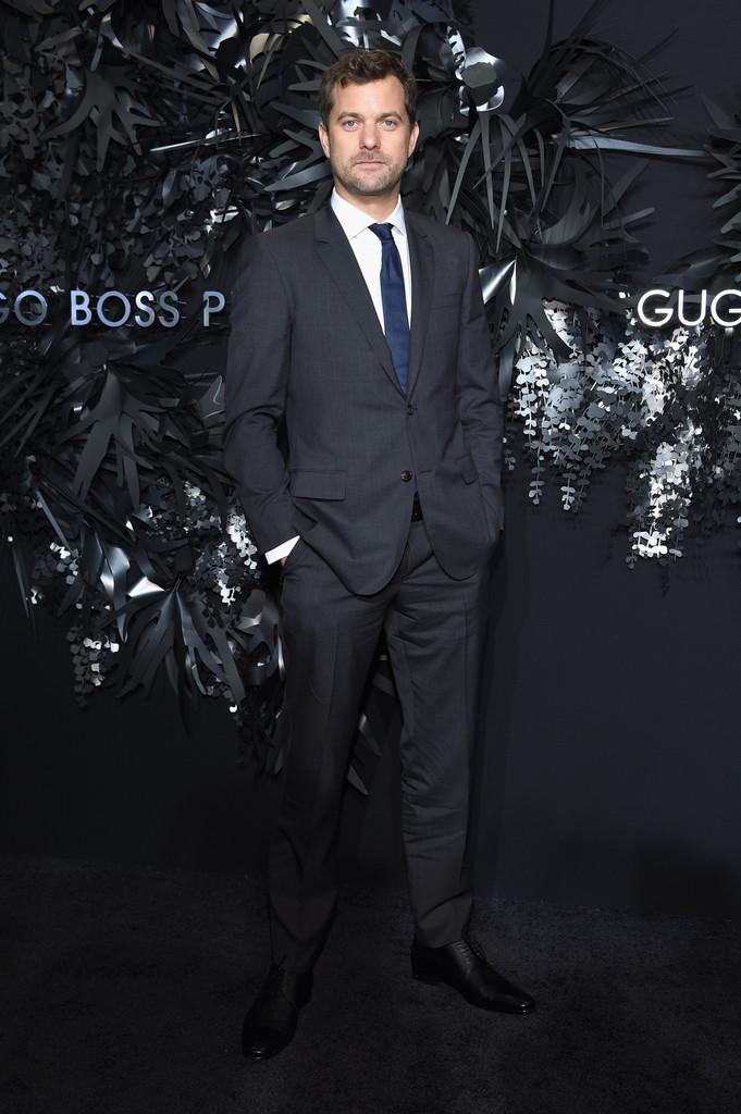 Adding a pop of color, actor Joshua Jackson sports a blue tie with a charcoal Hugo Boss suit.