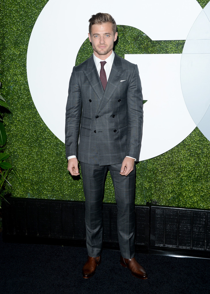 Robbie Rogers wears Gucci grey plaid peak lapel double-breasted New Signoria suit with a white shirt, red tie and brown leather boots.