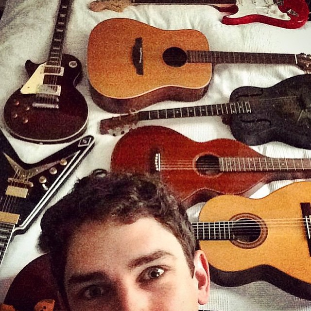 Arthur Gosse poses with quite the guitar collection.
