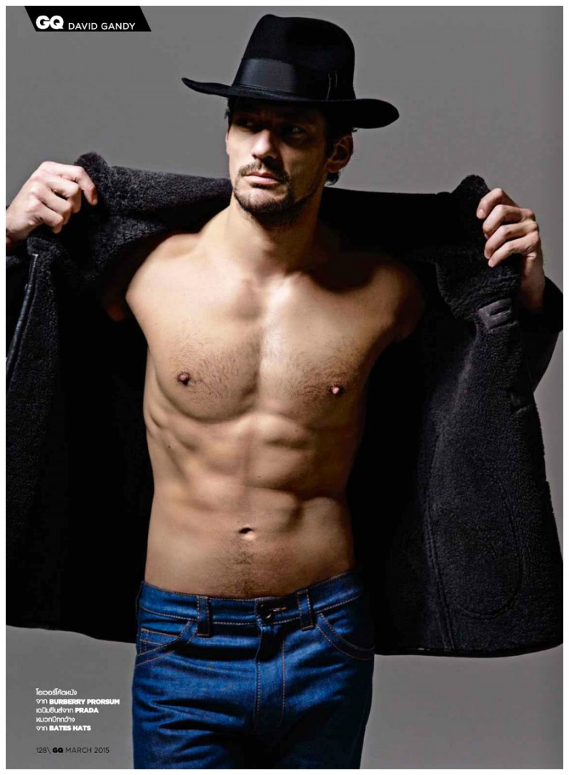 David Gandy opens his Burberry jacket to unveil his sculpted torso.