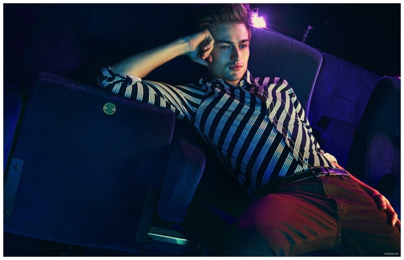 Douglas Booth poses for a relaxed photo in a striped top and leather belt from Prada.