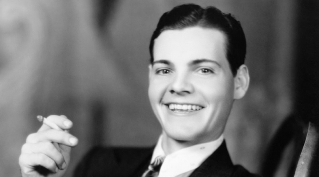 Flashing a smile, a young man in the 1920s wears a slick hairstyle featuring a side part.