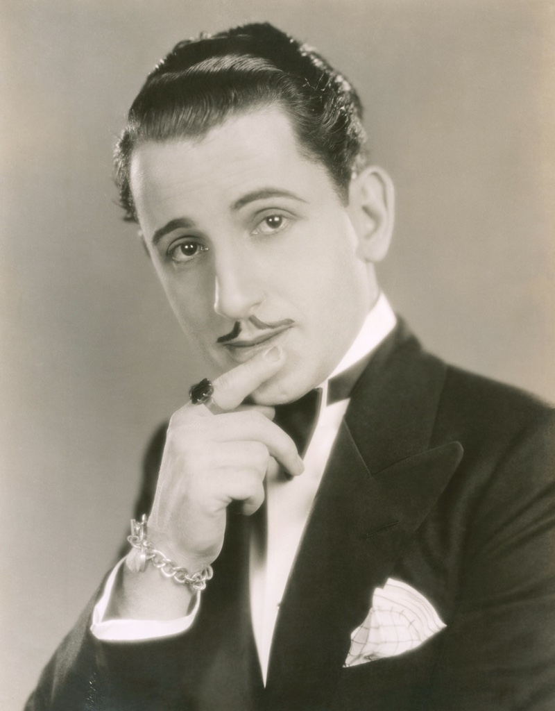 During the 1920s, men favored a clean shaven face or a small mustache. A man shows off a slicked back hairstyle with a thin mustache.