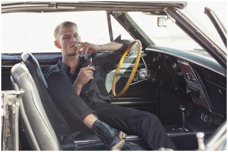 Sitting in a vintage car, Noah Teicher takes a smoke break.