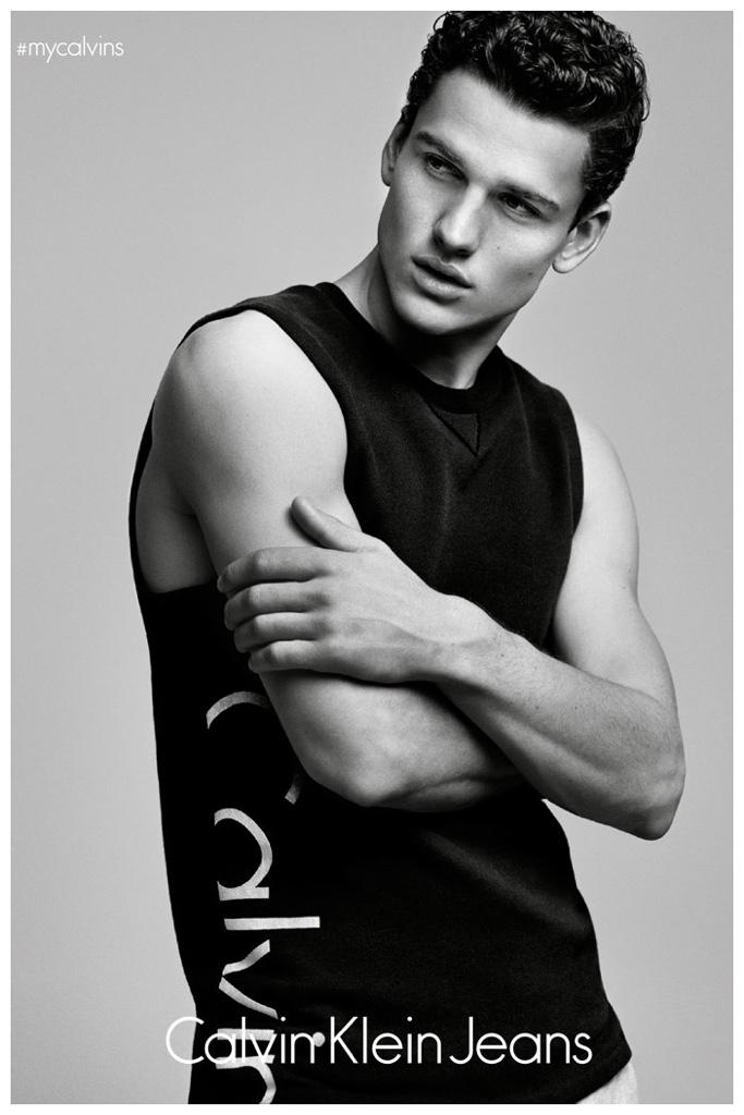 Simon Nessman poses in a Calvin Klein Jeans logo, sleeveless top.