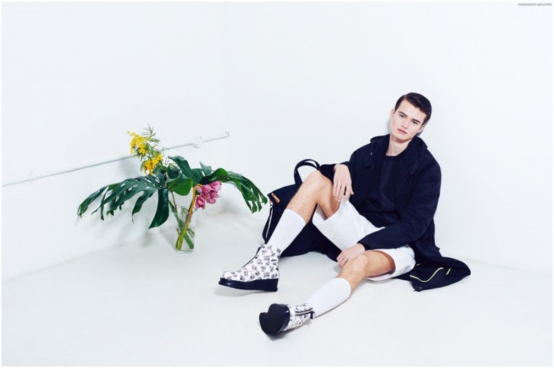 Reece wears coat Joanna Startek, t-shirt TXNMX, shorts Energie, printed boots Gioia Maini, socks Topman and bag Lacoste L!ve.