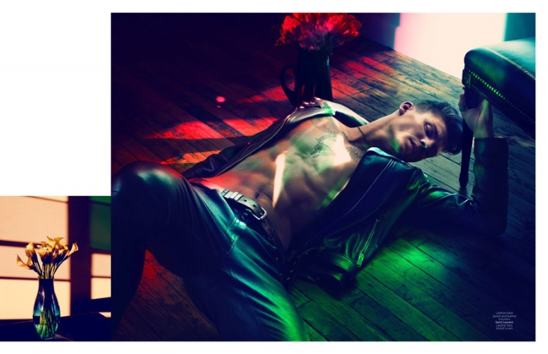 Laying on the floor, Mikkel Jensen is clad in leather.