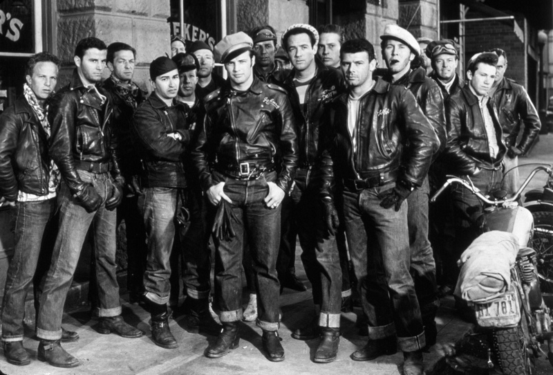 """Acting legend Marlon Brando poses on set of """"The Wild One"""" with his biker gang ensemble, perfecting the ideal rebellious look."""