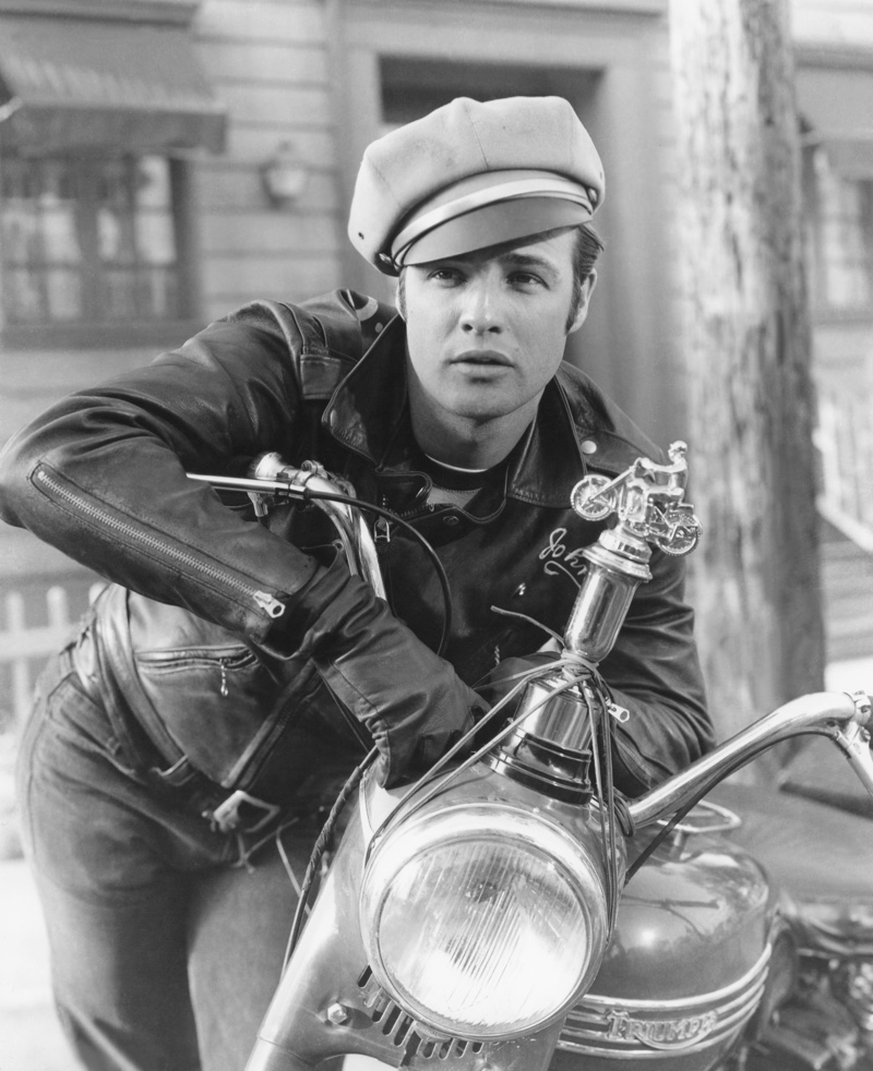 """In one of his most iconic roles and photos, Marlon Brando poses in character as bad boy Johnny Strabler in """"The Wild One."""" He sports his trademark leather biker jacket, jeans, and biker cap."""