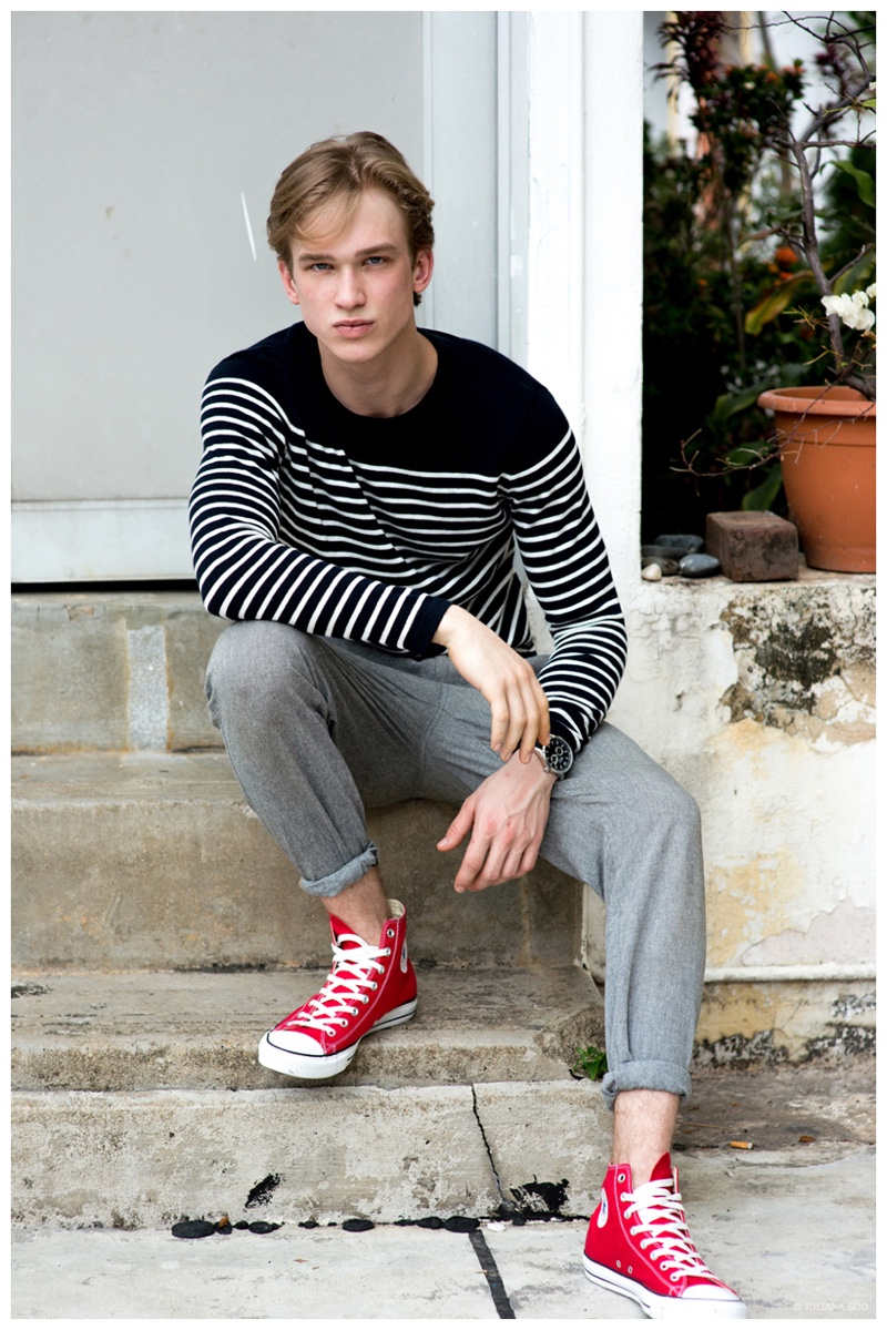 Sporting Converse and a casual ensemble from H&M, Mikal poses for an image outdoors.