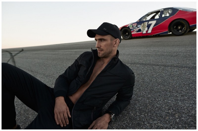 Will Chalker poses in a sleek racing-inspired jacket with a cap and black pants.