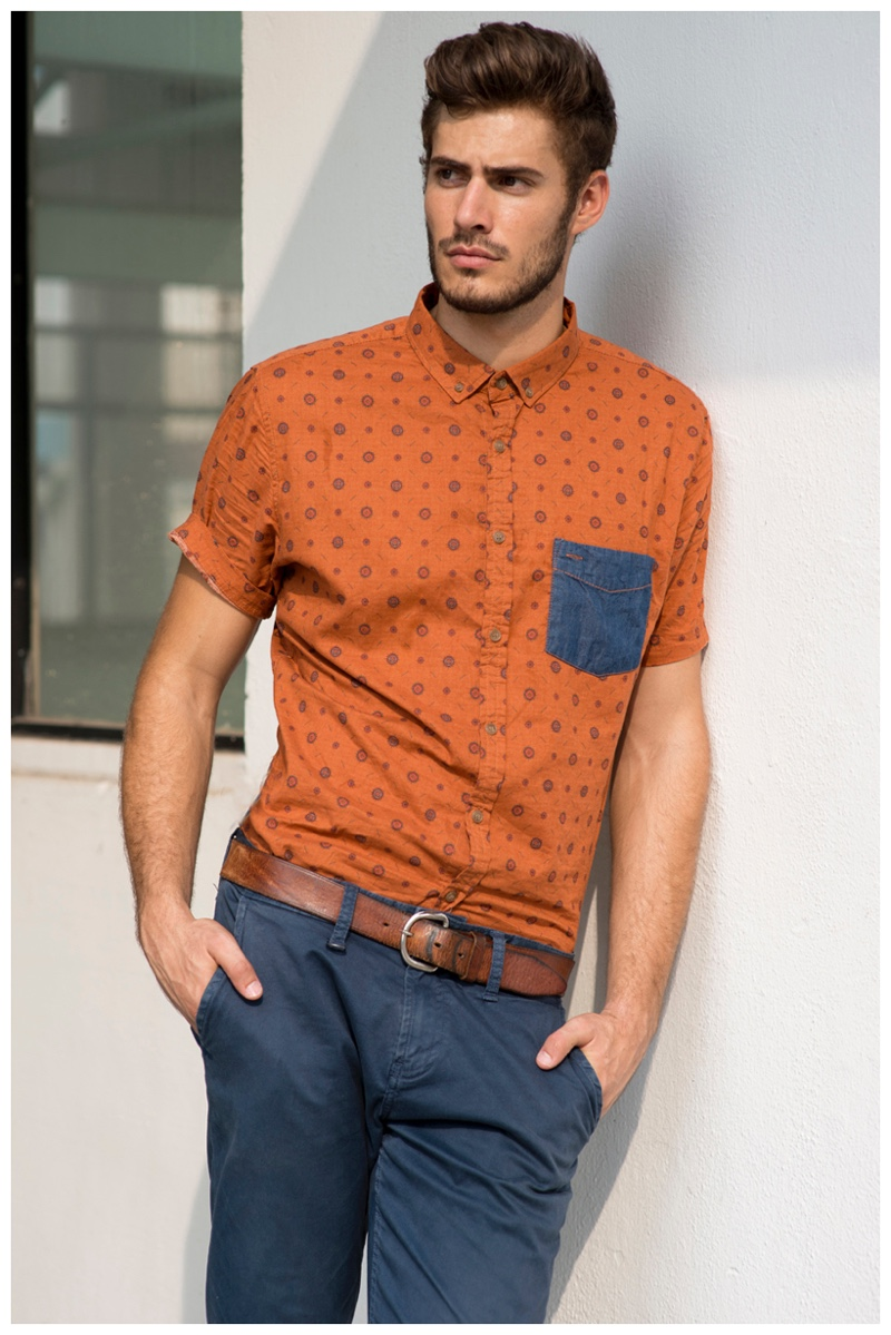 Adding a pop of color, Roelof Theunissen wears a short-sleeve print orange shirt.