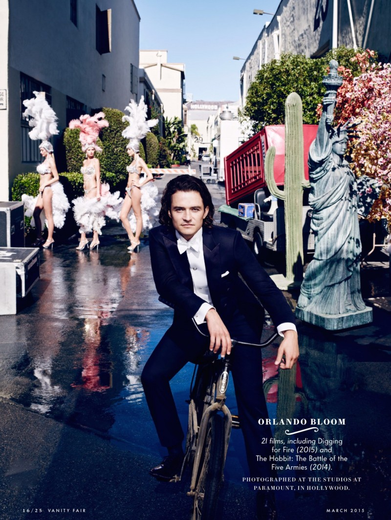 Orlando Bloom rides a bike as he poses with showgirls for Vanity Fair.