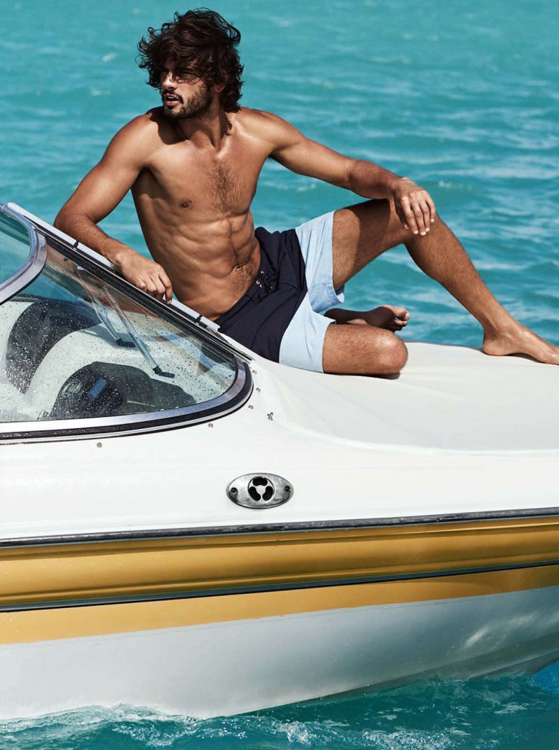 Marlon Teixeira relaxes on a boat, wearing colorblocked swim shorts from H&M.