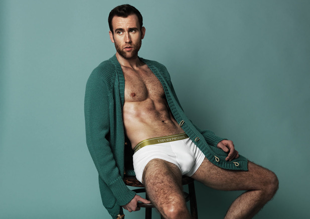 A shirtless Matthew Lewis poses in an oversized cardigan sweater and Emporio Armani underwear.
