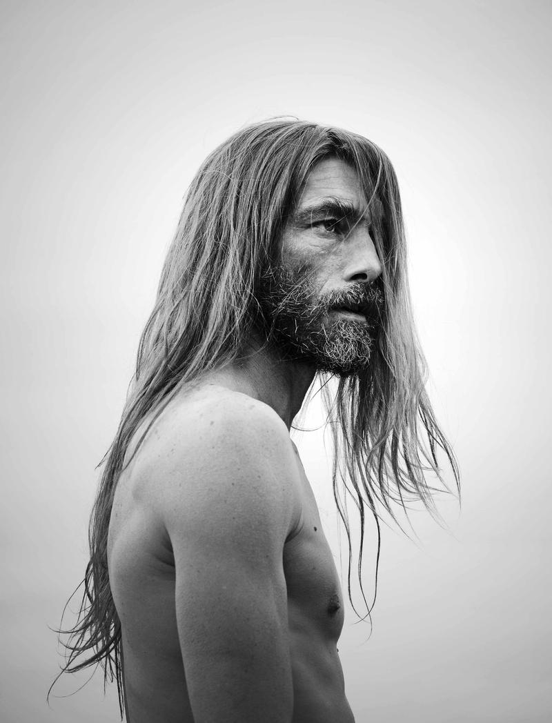 Patrick Petitjean lets his long hair down for a shirtless black & white portrait.