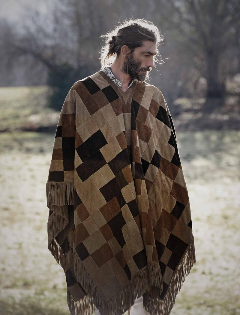 Pictured outdoors in a dramatic poncho, Patrick Petitjean rocks a trendy man bun.