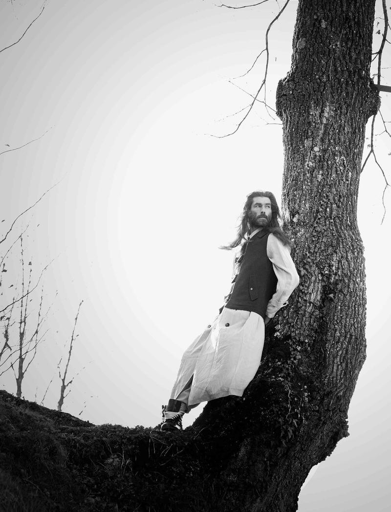 Embracing playful proportions, Patrick Petitjean poses on a high tree branch.