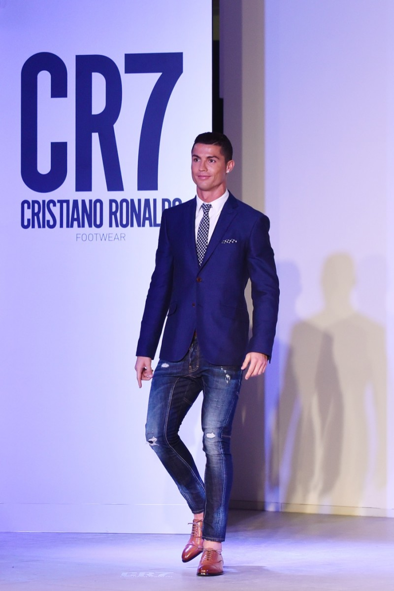 Cristiano Ronaldo hits the catwalk in a smart blazer, shirt and tie, paired with distressed skinny denim jeans and his own footwear.