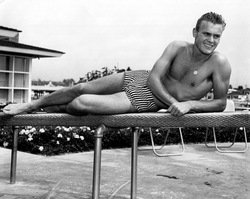 Tab Hunter relaxes in a striped swimsuit.