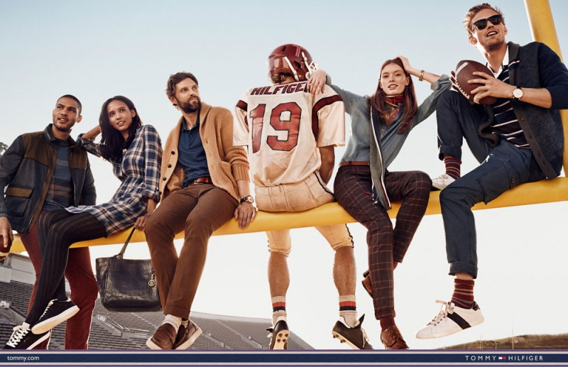Tommy Hilfiger hits a stylish stride on a football goal post.