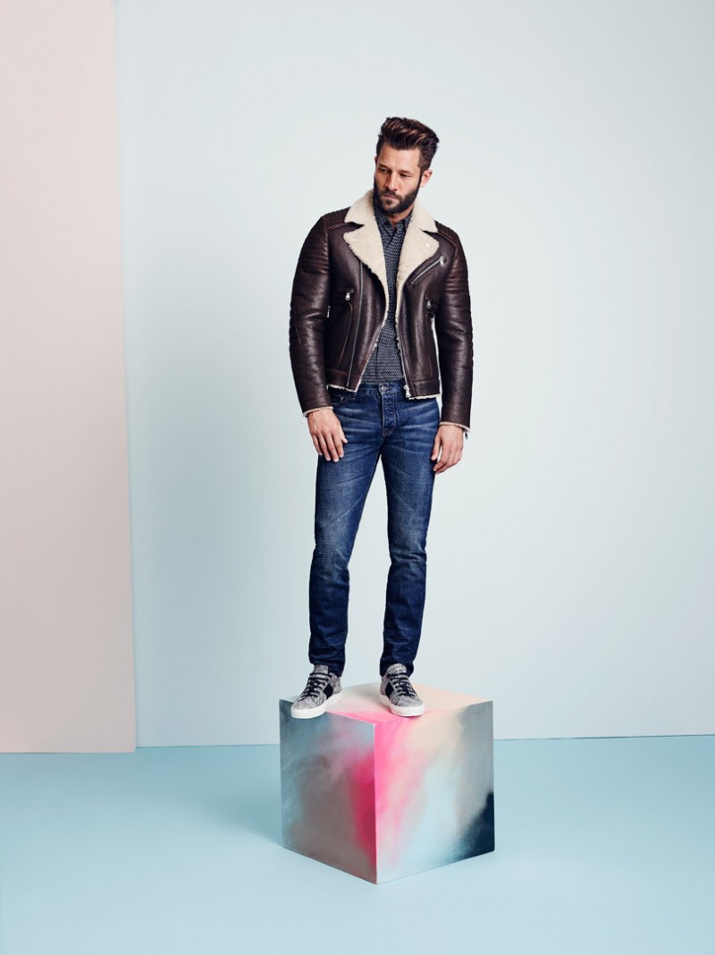 John goes casual in a leather jacket and distressed denim jeans.