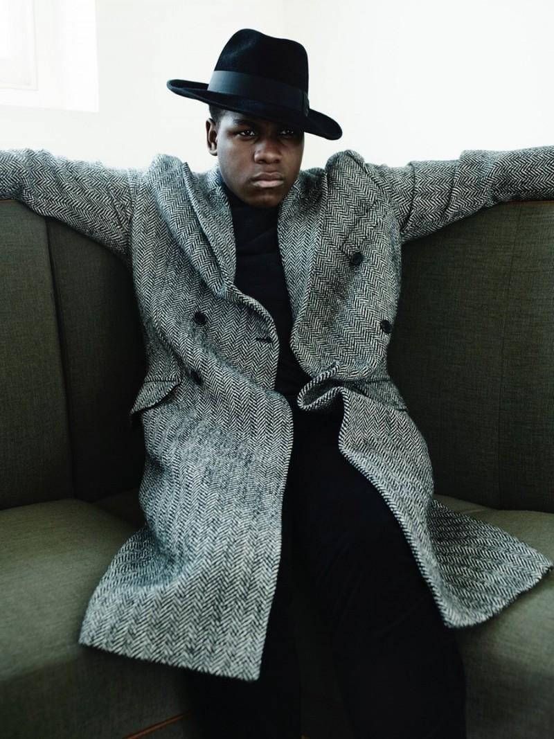 John Boyega relaxes in a double-breasted herringbone coat.