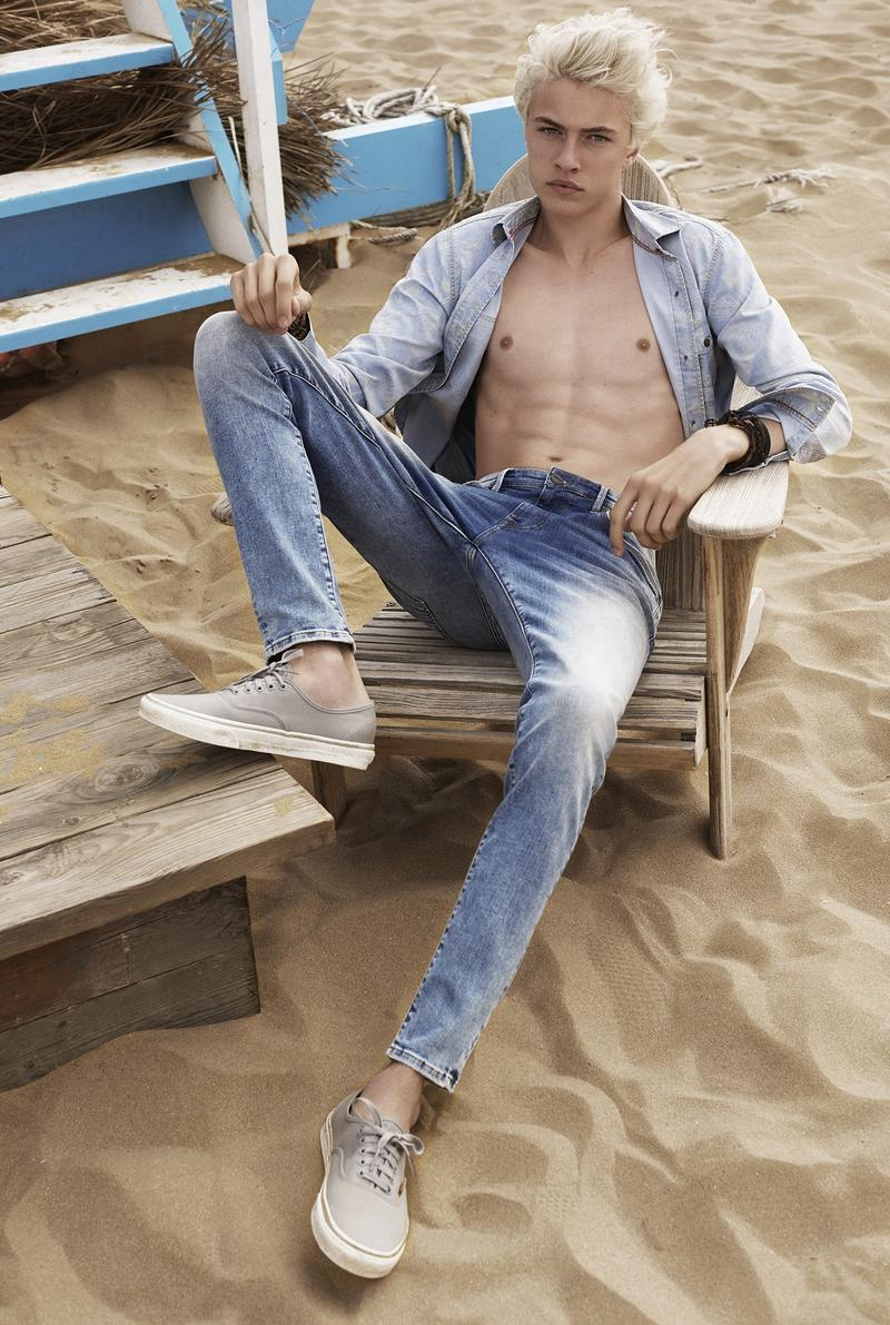 Lucky Blue Smith shows a little skin as he double up on denim for a photo at the beach.
